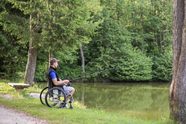 Disabled man on wheelchair fishing in nature Fishing as an accessible competitive sport for people with disabilities and also enjoying in nature for health benefits. paraplegic stock pictures, royalty-free photos & images