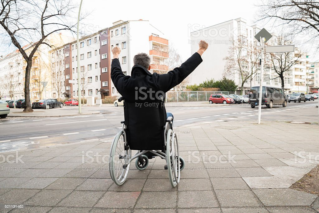 Disabled Man On Wheelchair With Hand Raised stock photo