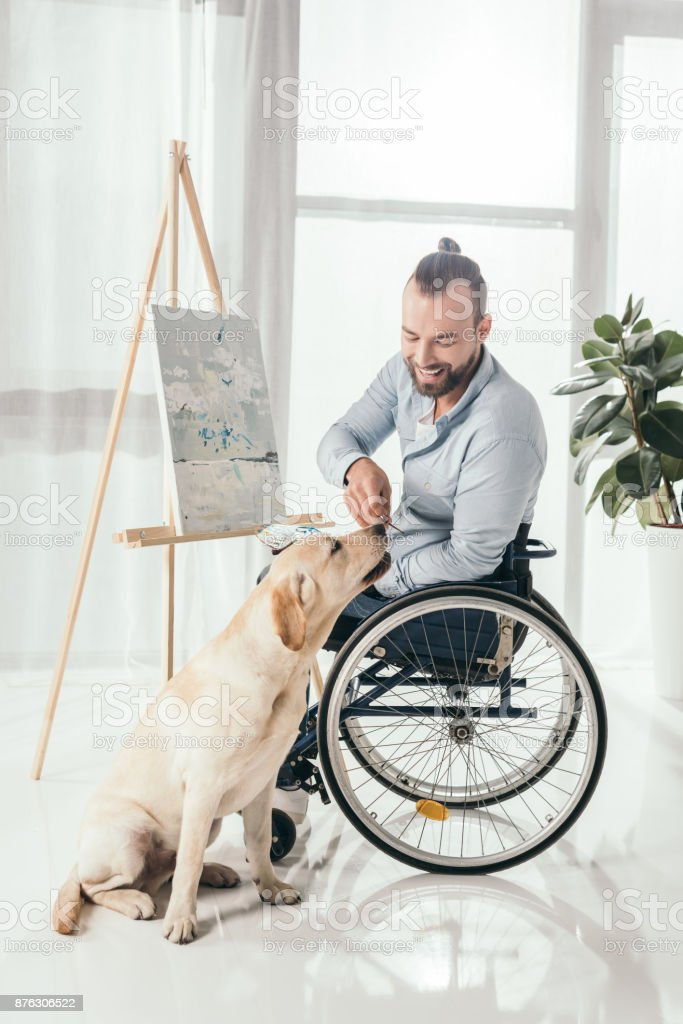 disabled man painting and petting dog stock photo