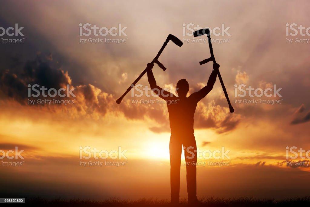 A disabled man raising his crutches at sunset. Cure, medical miracle. royalty-free stock photo