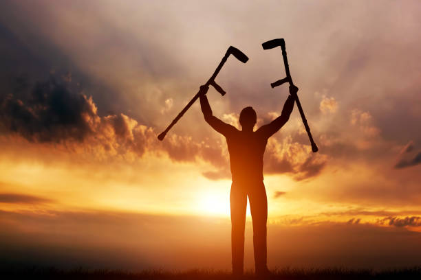 A disabled man raising his crutches at sunset. Cure, medical miracle. stock photo