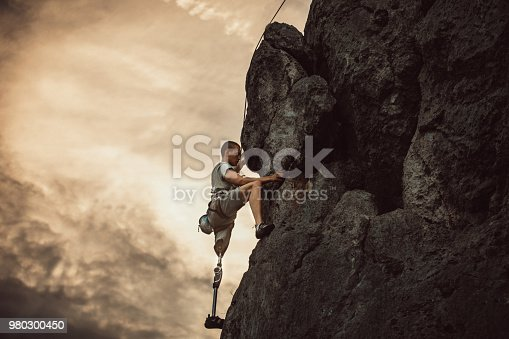 Man with prosthetic leg free mountain climbing.