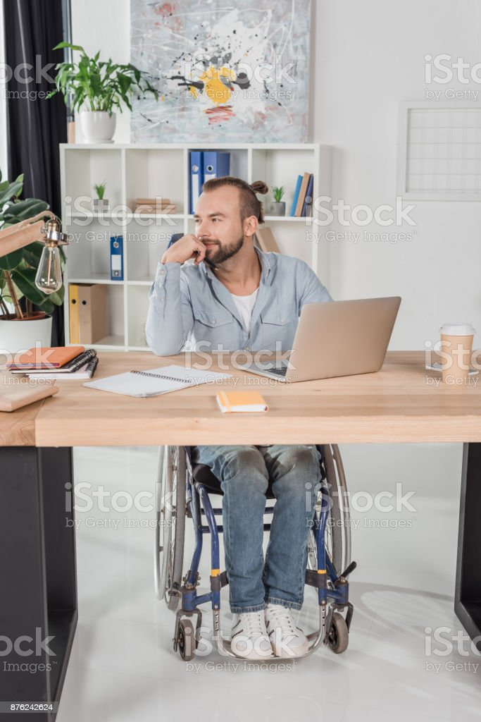 disabled man sitting at workplace stock photo