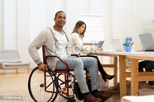 istock Disabled man sitting in a wheelchair at workplace 1076818140