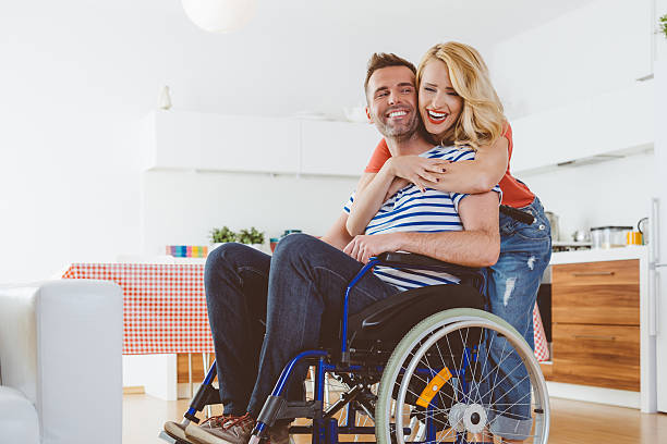 disabled man sitting in a wheelchair, his wife embracing him - wheelchair stock photos and pictures