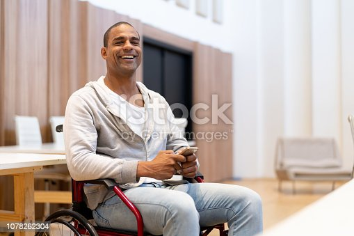 istock Disabled man sitting in a wheelchair using mobile at workplace 1078262304