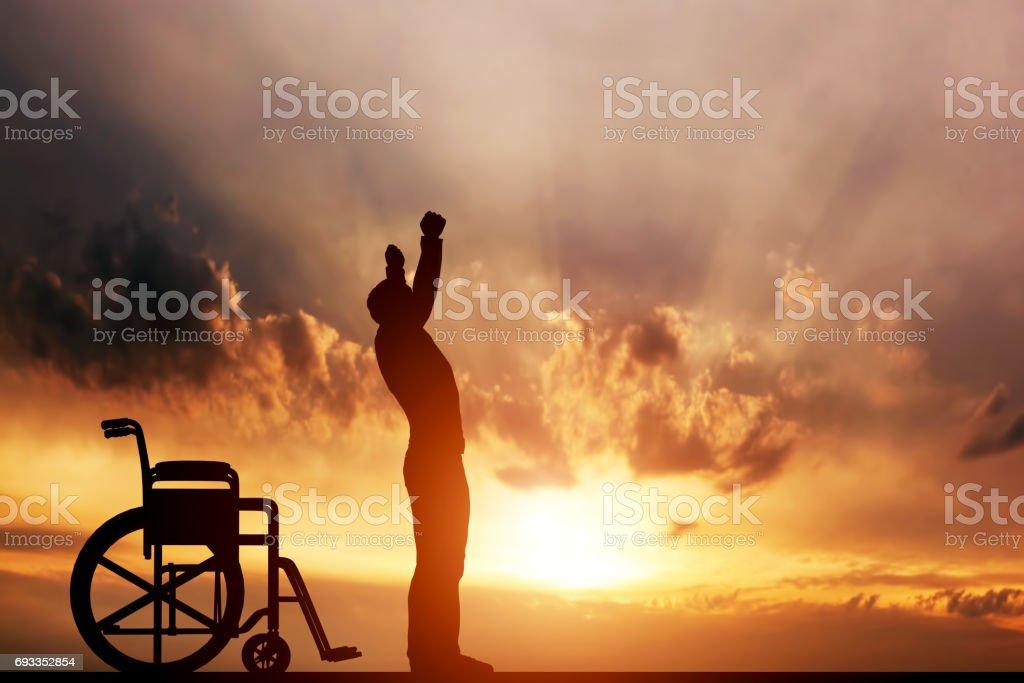 Un hombre discapacitado levantarse desde una silla de ruedas. Curación, milagro médico. - foto de stock