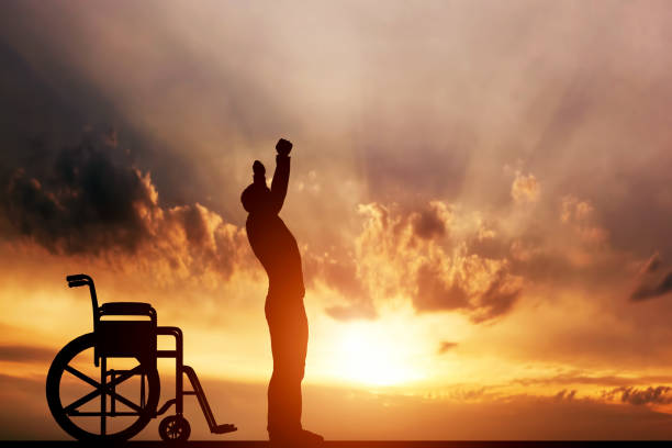 A disabled man standing up from wheelchair. Cure, medical miracle. stock photo