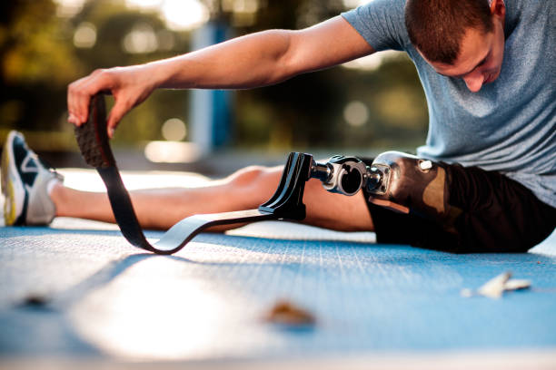 Disabled man stretching outdoors Close up low angle view of male athlete with prosthetic leg during stretching exercise. prosthetic hand stock pictures, royalty-free photos & images