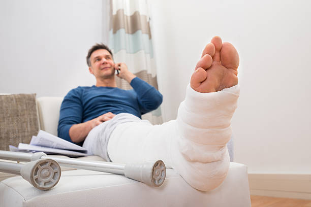 disabled man talking on cellphone - broken leg stock photos and pictures