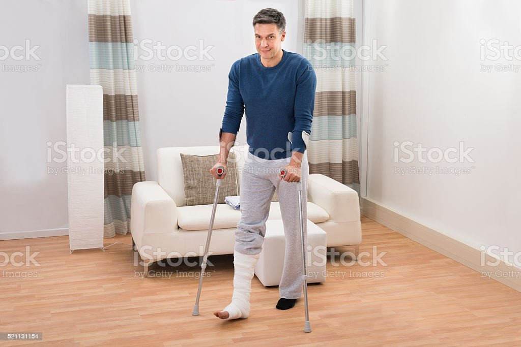 Disabled Man Using Crutches For Walking stock photo