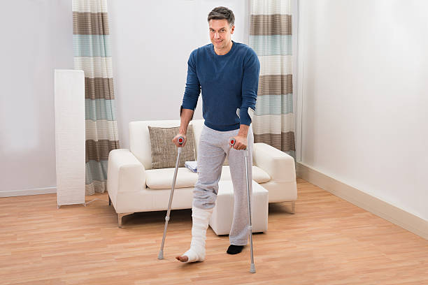 disabled man using crutches for walking - broken leg stock photos and pictures