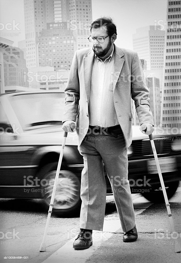 Disabled man using crutches, walking in street (B&W) royalty free stockfoto