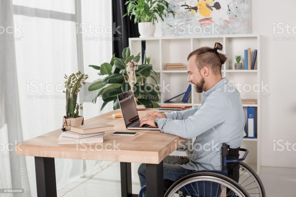disabled man using laptop stock photo
