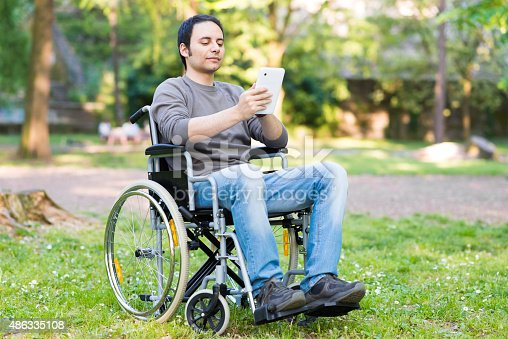 istock Disabled man using tablet in a park 486335108