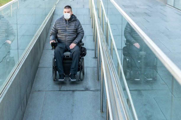 Disabled man wearing protection face mask stock photo