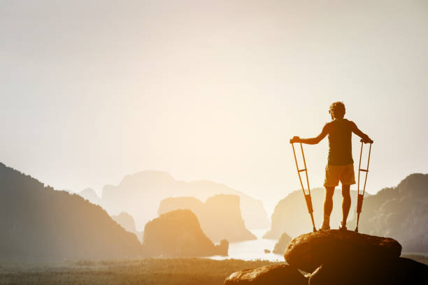 Disabled man with crutches on big rock stands like winner stock photo
