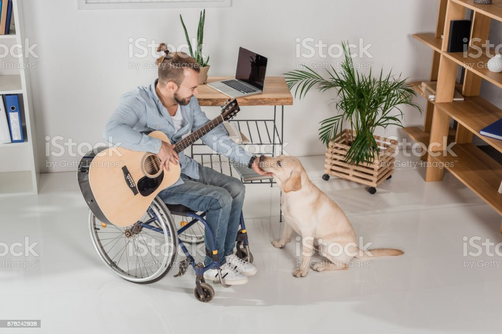 disabled man with guitar petting dog stock photo