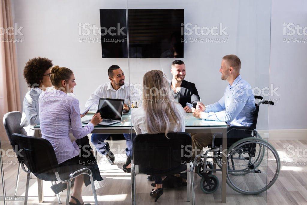 Gerente de movilidad sentado con sus compañeros foto de stock libre de derechos