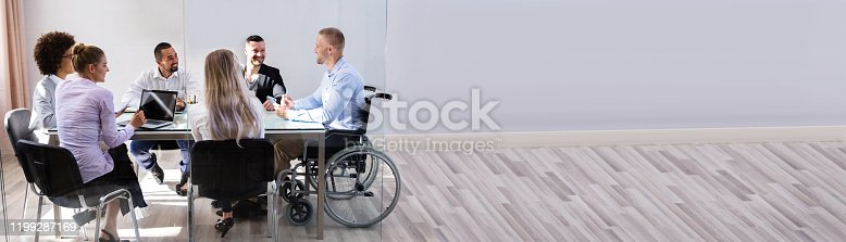istock Disabled Manager Sitting With His Colleagues 1199287169