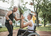 istock Disabled men playing basketball with friends 1278616440