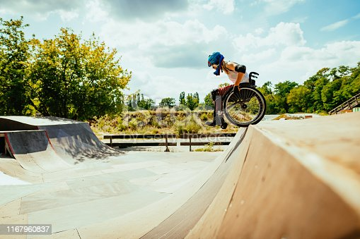 Wheelchair woman performing stunts in skate park - courage and confidence in adaptive sports and hobbies