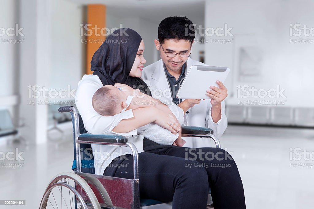 Disabled mother and doctor with tablet stock photo