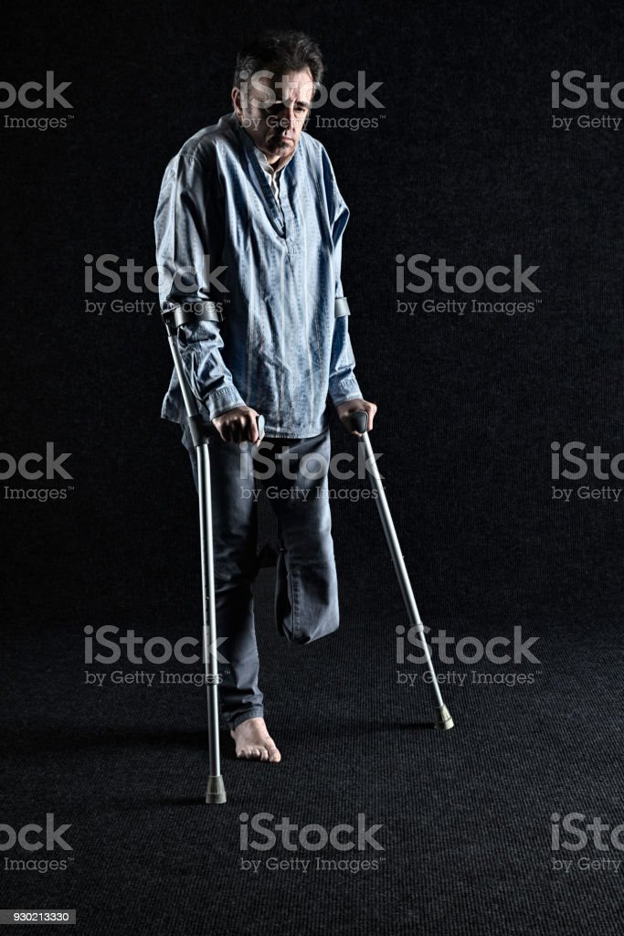 Disabled one-legged man on crutches stock photo