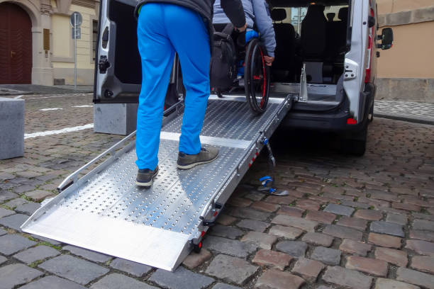 Disabled person on wheelchair using car lift stock photo