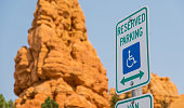 Disabled persons parking sign with eroded rocks of Red Canyon National Park, Utah as background