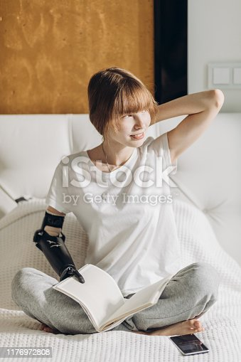 istock disabled pleasant girl with a favourite book looking aside 1176972808