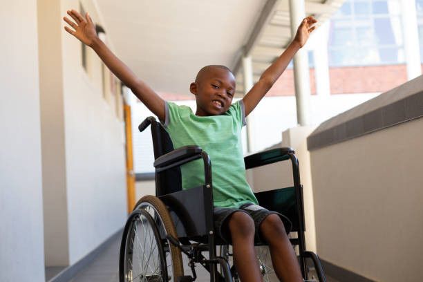 Disabled schoolboy arms stretched out in a corridor stock photo
