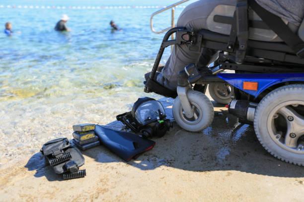 Disabled scuba diver on beach shore stock photo