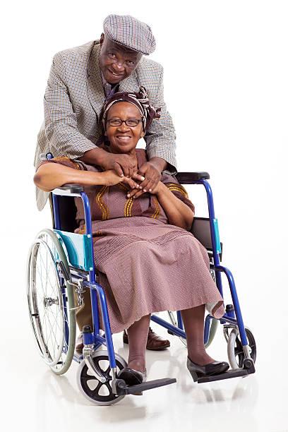 senior mujer africana con discapacidades y su personal atento marido - foto de stock