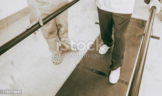 Disabled senior helped by the physiotherapist is doing rehabilitation on the footboard.