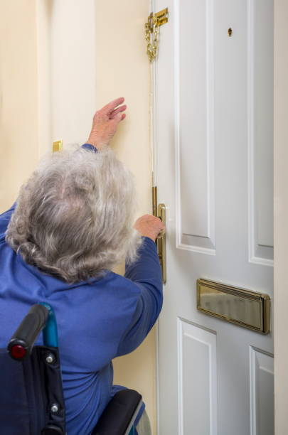 Disabled Senior Lady trying to open a door. stock photo