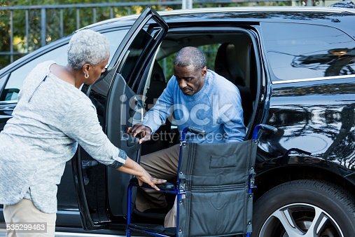 466456685 istock photo Disabled senior man getting from car to wheelchair 535299463