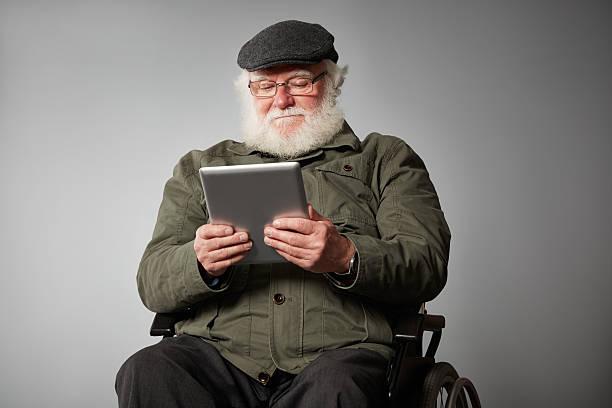 Behinderte senior Mann auf Rollstuhl benutzen tablet PC – Foto