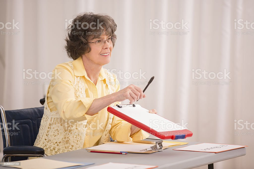 Disabled senior woman at conference or voter registration table. stock photo