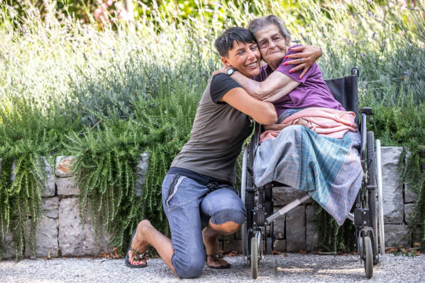Disabled Senior Woman On Wheelchair Is Always Happy To Receive Visits stock photo