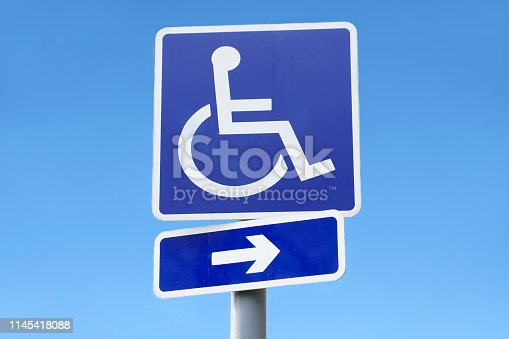istock Disabled sign of wheelchair and direction arrow against empty clear blue sky 1145418088