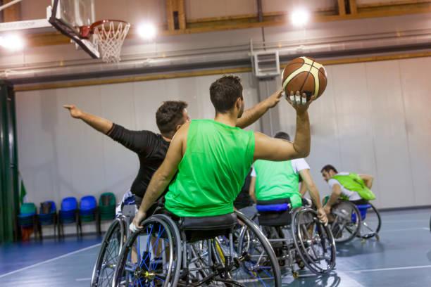 personnes handicapées sport hommes dans l'action tout en jouant au basket-ball indoor - sports en fauteuil roulant photos et images de collection