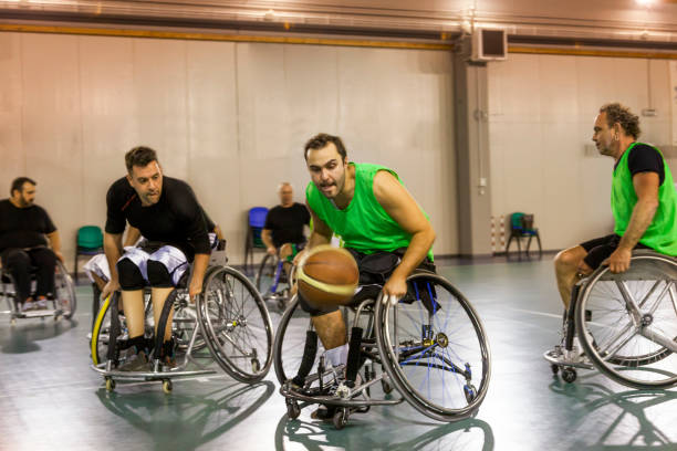 disabled sport men in action while playing indoor basketball - wheelchair sports stock photos and pictures