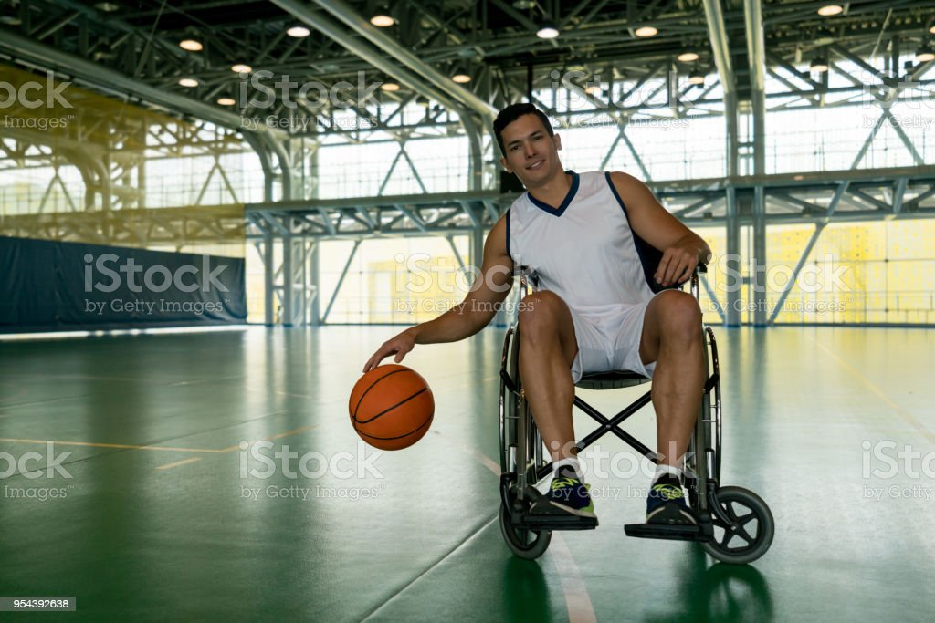 Deportista con discapacidad botando el balón mientras mira a la cámara sonriendo - foto de stock