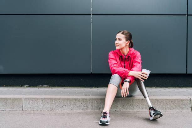 funktionshindrade idrottskvinna lyssnar musik i hörlurar och hålla kopp på gatan - protesutrustning bildbanksfoton och bilder