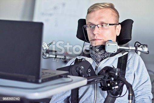 Disabled student in class room working with laptop.