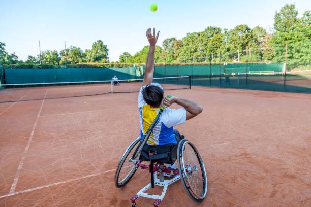 joueuse de tennis handicapés frappe la balle - sports en fauteuil roulant photos et images de collection