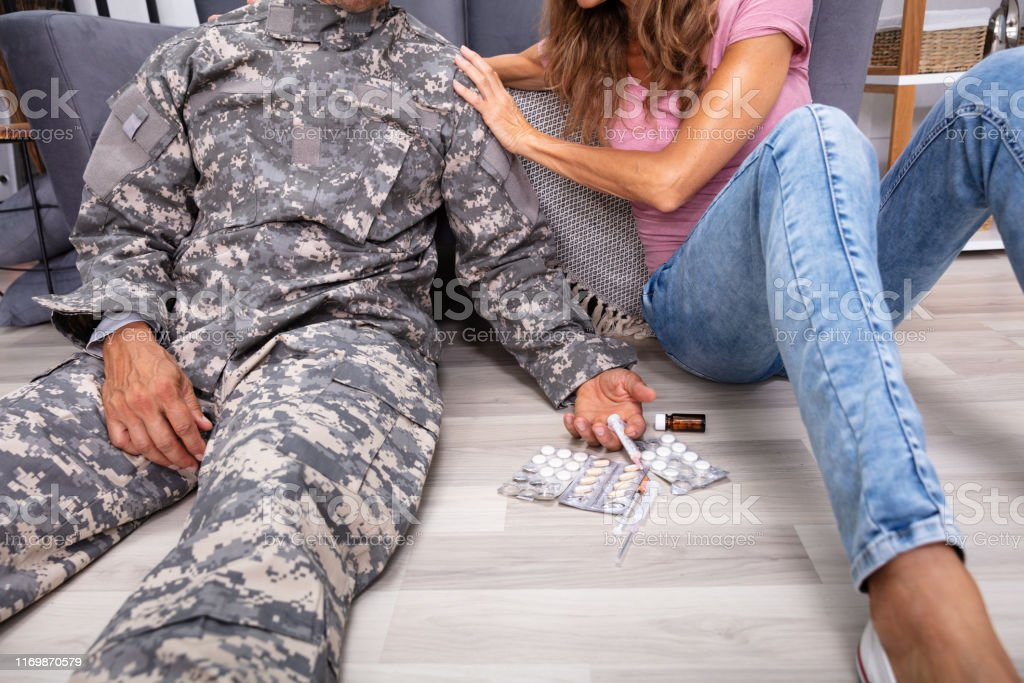 Disabled Veteran Sitting On Floor With Syringe And Pills - Royalty-free Addiction Stock Photo