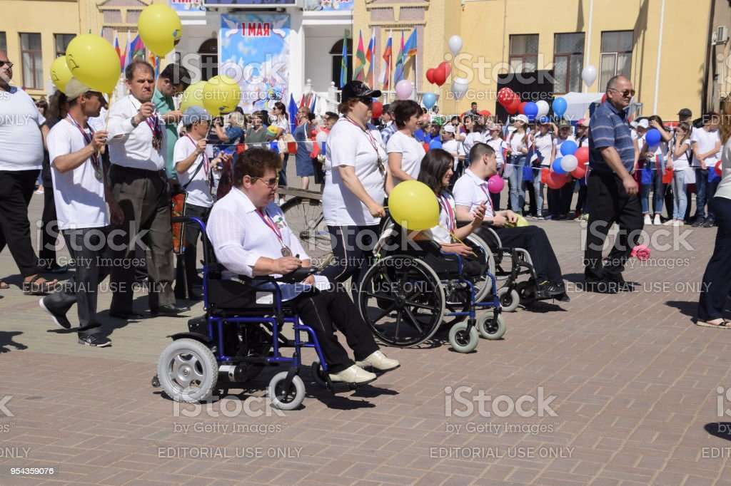 Disabled wheelchair users on a festive procession. Celebrating the first of May, the day of spring and work. May Day parade on the Theater Square in the city of Slavyansk-on-Kuban. stock photo