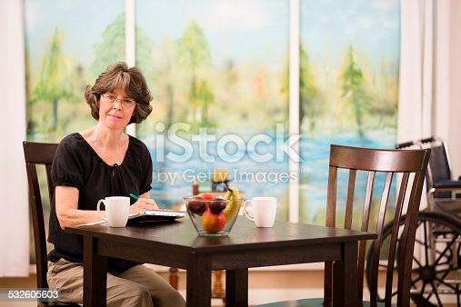 istock Disabled woman fills out insurance claim form. Home. Wheelchair. 532605603